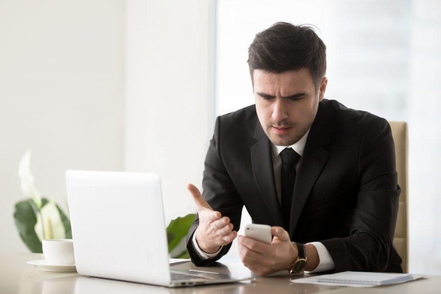 irritated man looking at phone
