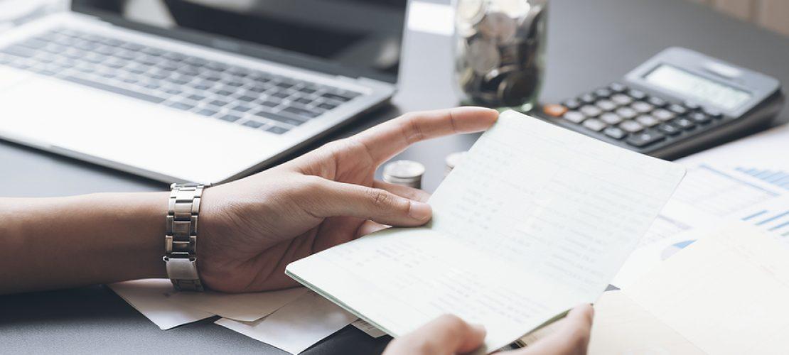 Accountant hands holding saving account passbook, book bank. Business account saving concept.