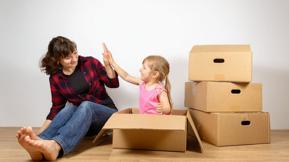 Mom and daughter put things out of the boxes after moving to a new house. The joy of buying new homes