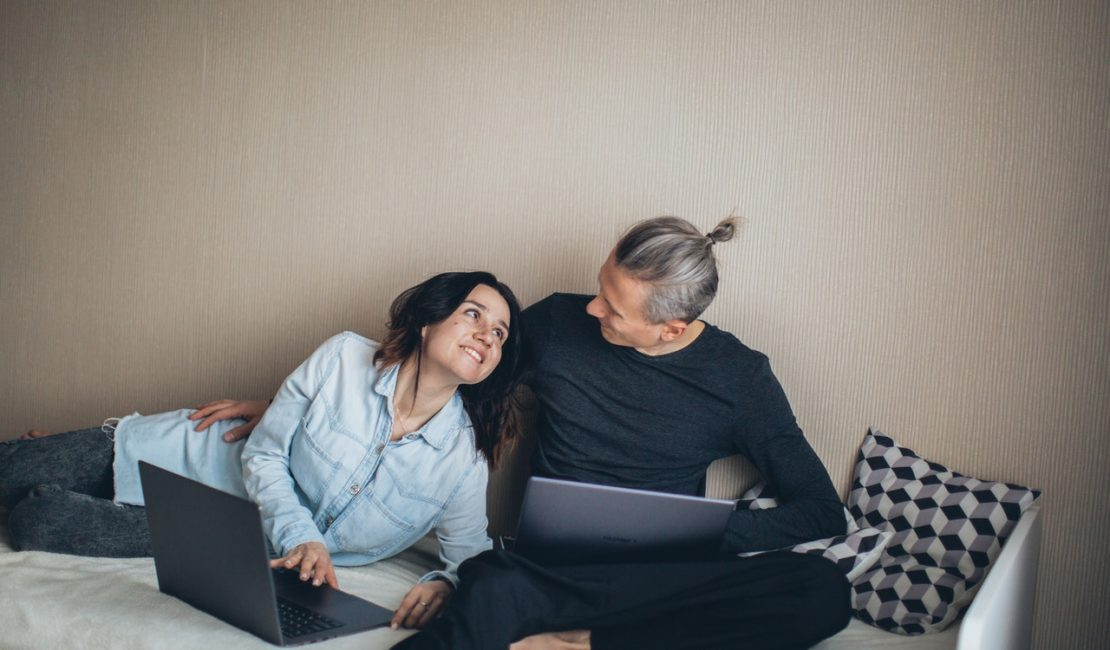 couple-sitting-on-the-bed-working-4008774