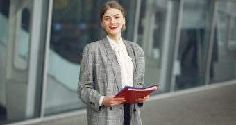 happy-female-manager-with-papers-near-office-building-3885528