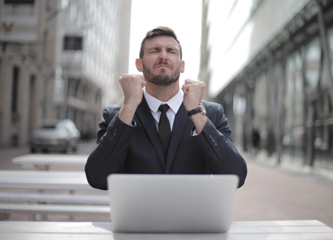 man-in-black-suit-sitting-on-chair-beside-buildings-3778966
