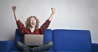 photo-of-excited-person-with-hands-up-sitting-on-a-blue-sofa-3770000