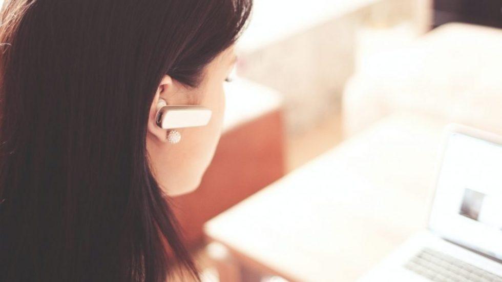 woman-wearing-earpiece-using-white-laptop-computer-210647