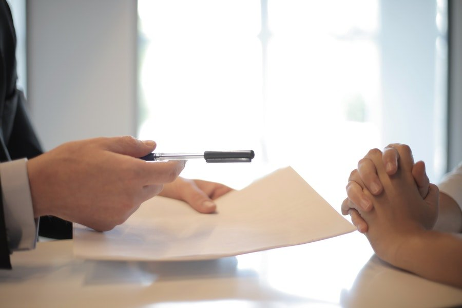 man handing a pen and paper to another person